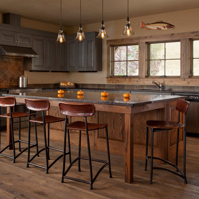 Inspiration for a mid-sized rustic l-shaped dark wood floor kitchen remodel in Other with an undermount sink, raised-panel cabinets, brown cabinets, brown backsplash, stainless steel appliances and an island