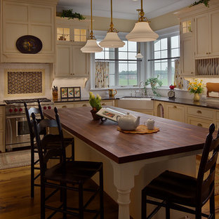 Example of a large farmhouse u-shaped medium tone wood floor eat-in kitchen design in Detroit with a farmhouse sink, flat-panel cabinets, white cabinets, granite countertops, white backsplash, subway tile backsplash, an island and stainless steel appliances