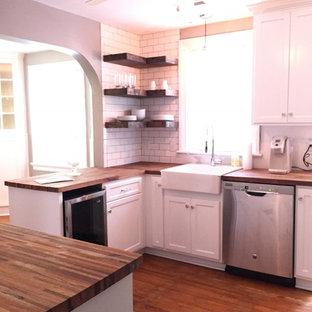 Mittelgroße Landhaus Wohnküche ohne Insel in U-Form mit Landhausspüle, Schrankfronten im Shaker-Stil, weißen Schränken, Arbeitsplatte aus Holz, Küchenrückwand in Weiß, Küchengeräten aus Edelstahl, braunem Holzboden und braunem Boden in Richmond