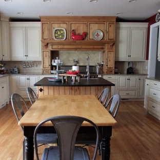 Large country u-shaped eat-in kitchen in New York with with island, raised-panel cabinets, white cabinets, beige splashback, stainless steel appliances, light hardwood floors, brown floor, multi-coloured benchtop, a farmhouse sink, soapstone benchtops and ceramic splashback.