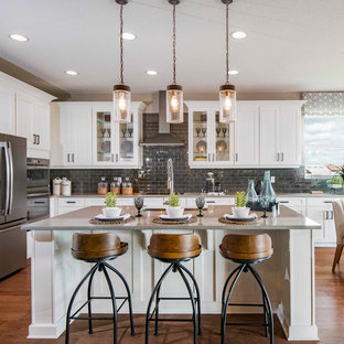 Farmhouse eat-in kitchen designs - Eat-in kitchen - farmhouse l-shaped medium tone wood floor and brown floor eat-in kitchen idea in Orlando with white cabinets, quartzite countertops, gray backsplash, glass tile backsplash, stainless steel appliances, an island, gray countertops and shaker cabinets