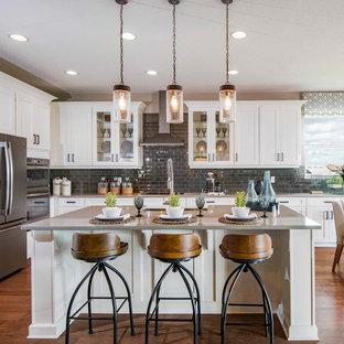 オーランドのカントリー風おしゃれなキッチン (白いキャビネット、珪岩カウンター、グレーのキッチンパネル、ガラスタイルのキッチンパネル、シルバーの調理設備の、無垢フローリング、茶色い床、グレーのキッチンカウンター、シェーカースタイル扉のキャビネット) の写真