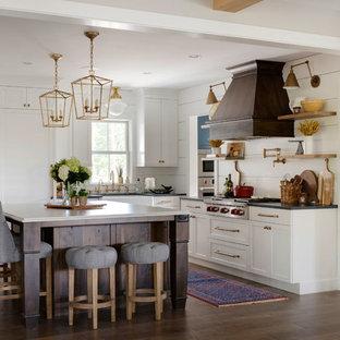 ミネアポリスの大きいカントリー風おしゃれなキッチン (エプロンフロントシンク、シルバーの調理設備の、シェーカースタイル扉のキャビネット、白いキャビネット、濃色無垢フローリング、茶色い床、グレーのキッチンカウンター、クオーツストーンカウンター、白いキッチンパネル) の写真