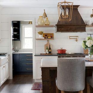 Große Landhausstil Wohnküche mit Landhausspüle, Küchengeräten aus Edelstahl, Kücheninsel und Rückwand aus Holzdielen in Minneapolis