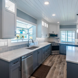 This is an example of a mid-sized traditional l-shaped open plan kitchen in Vancouver with an undermount sink, shaker cabinets, blue cabinets, quartz benchtops, blue splashback, subway tile splashback, stainless steel appliances, vinyl floors, with island, brown floor and white benchtop.