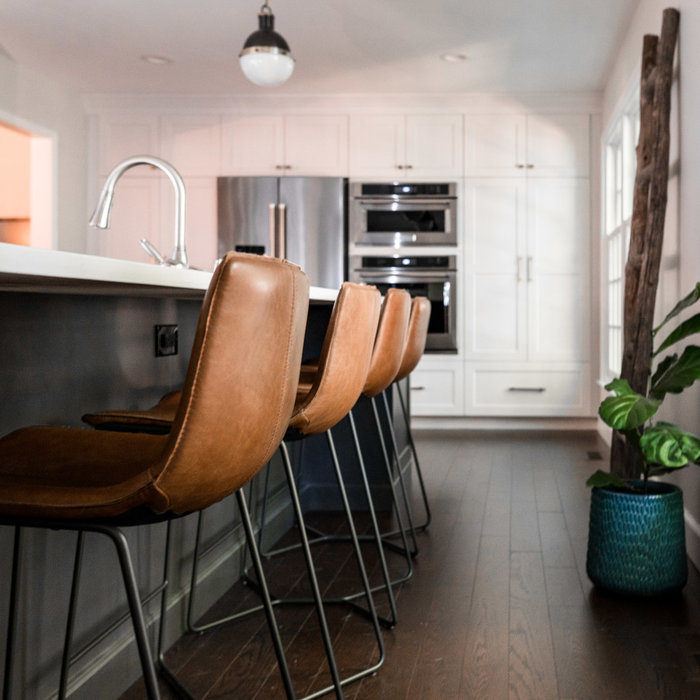 By removing cabinet along one of the walls in this kitchen, we were able to create a light and airy space with larger windows that extend down to the floor as well as create a long island for seating.