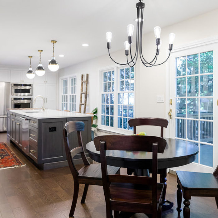 Example of a country l-shaped dark wood floor and brown floor eat-in kitchen design in Detroit with an undermount sink, shaker cabinets, white cabinets, quartz countertops, gray backsplash, porcelain