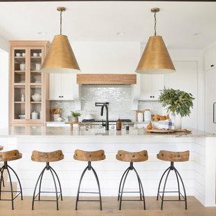 ミネアポリスのカントリー風おしゃれなアイランドキッチン (シェーカースタイル扉のキャビネット、白いキャビネット、白いキッチンパネル、パネルと同色の調理設備、淡色無垢フローリング、ベージュのキッチンカウンター) の写真