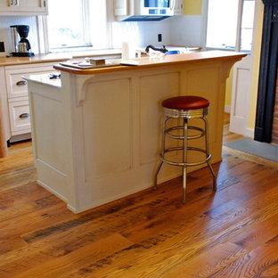 ニューヨークのカントリー風おしゃれなキッチン (ドロップインシンク、フラットパネル扉のキャビネット、白いキャビネット、木材カウンター、無垢フローリング) の写真