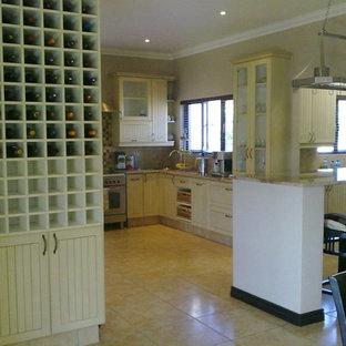 他の地域のカントリー風おしゃれなキッチン (シングルシンク、フラットパネル扉のキャビネット、ヴィンテージ仕上げキャビネット、御影石カウンター、モザイクタイルのキッチンパネル、シルバーの調理設備、セラミックタイルの床) の写真