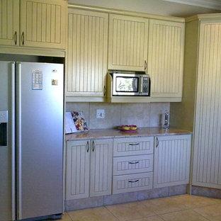 他の地域のカントリー風おしゃれなキッチン (フラットパネル扉のキャビネット、ヴィンテージ仕上げキャビネット、御影石カウンター、モザイクタイルのキッチンパネル、シルバーの調理設備、セラミックタイルの床、アイランドなし) の写真