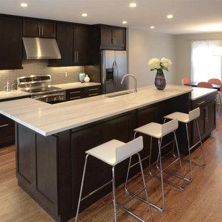 Klassisk inredning av ett kök, med rostfria vitvaror, en undermonterad diskho, skåp i shakerstil, skåp i mörkt trä och stänkskydd i glaskakel