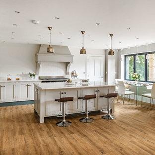 Klassische Wohnküche in L-Form mit Schrankfronten im Shaker-Stil, weißen Schränken, Küchenrückwand in Weiß, Rückwand aus Metrofliesen, Küchengeräten aus Edelstahl, hellem Holzboden und Kücheninsel in Surrey