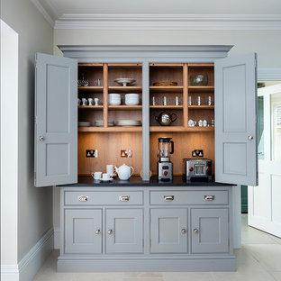 Modelo de cocina clásica renovada, grande, con puertas de armario grises, suelo de piedra caliza, suelo beige, armarios estilo shaker, salpicadero de madera y encimeras negras