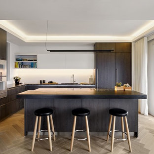 Design ideas for a medium sized contemporary l-shaped kitchen in London with a submerged sink, flat-panel cabinets, dark wood cabinets, granite worktops, white splashback, stainless steel appliances, light hardwood flooring, an island, beige floors and black worktops.