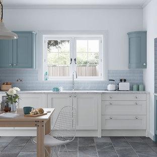 マンチェスターの中くらいのカントリー風おしゃれなキッチン (シェーカースタイル扉のキャビネット、白いキャビネット、青いキッチンパネル、サブウェイタイルのキッチンパネル、アイランドなし、ドロップインシンク、大理石カウンター、セラミックタイルの床、白い調理設備) の写真