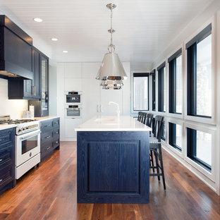 Einzeilige, Mittelgroße Klassische Wohnküche mit Unterbauwaschbecken, profilierten Schrankfronten, blauen Schränken, Quarzwerkstein-Arbeitsplatte, Küchenrückwand in Weiß, Rückwand aus Metrofliesen, weißen Elektrogeräten, dunklem Holzboden, Kücheninsel und braunem Boden in Sonstige