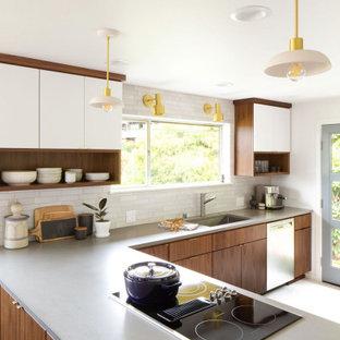 Идея дизайна: угловая кухня среднего размера в стиле ретро с врезной раковиной, плоскими фасадами, фасадами цвета дерева среднего тона, серым фартуком, полуостровом, белым полом и серой столешницей