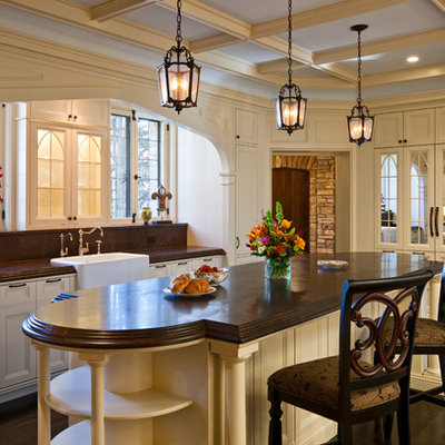 Mid-sized elegant single-wall dark wood floor and brown floor enclosed kitchen photo in Minneapolis with a farmhouse sink, recessed-panel cabinets, brown backsplash, an island, white cabinets, quartz countertops, stone slab backsplash, paneled appliances and brown countertops