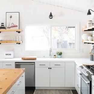 サクラメントのカントリー風おしゃれなキッチン (一体型シンク、フラットパネル扉のキャビネット、白いキャビネット、白いキッチンパネル、サブウェイタイルのキッチンパネル、シルバーの調理設備、茶色い床、白いキッチンカウンター) の写真