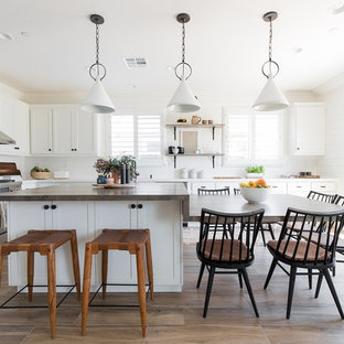 Farmhouse eat-in kitchen remodeling - Inspiration for a farmhouse l-shaped medium tone wood floor and brown floor eat-in kitchen remodel in Sacramento with shaker cabinets, white cabinets, wood countertops, red backsplash, subway tile backsplash, stainless steel appliances, an island and brown countertops
