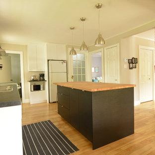 Exempel på ett litet industriellt kök, med släta luckor, träbänkskiva, stänkskydd i glaskakel, ljust trägolv och en köksö