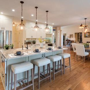 Große Klassische Wohnküche in L-Form mit Landhausspüle, Schrankfronten im Shaker-Stil, weißen Schränken, Granit-Arbeitsplatte, Rückwand aus Metrofliesen, Küchengeräten aus Edelstahl, braunem Holzboden, Kücheninsel, braunem Boden, beiger Arbeitsplatte und Küchenrückwand in Braun in Atlanta