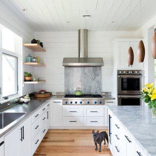 Klassische Küche in L-Form mit integriertem Waschbecken, Schrankfronten im Shaker-Stil, weißen Schränken, Edelstahl-Arbeitsplatte, Küchenrückwand in Grau, Küchengeräten aus Edelstahl, braunem Holzboden, Kücheninsel und Rückwand aus Marmor in Austin