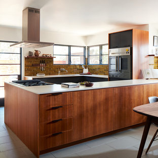 Midcentury u-shaped eat-in kitchen in San Francisco with an undermount sink, flat-panel cabinets, medium wood cabinets, brown splashback, black appliances, a peninsula, grey floor and white benchtop.