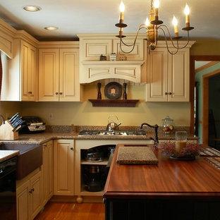 ボストンのカントリー風おしゃれなキッチン (エプロンフロントシンク、レイズドパネル扉のキャビネット、黄色いキャビネット、クオーツストーンカウンター、黄色いキッチンパネル、黒い調理設備、無垢フローリング) の写真