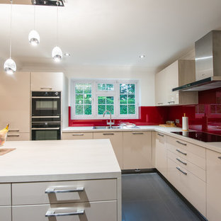 Contemporary kitchen photos - Trendy l-shaped kitchen photo in London with a double-bowl sink, flat-panel cabinets, light wood cabinets, onyx countertops, red backsplash, glass sheet backsplash, black appliances and an island