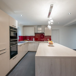 Contemporary kitchen appliance - Kitchen - contemporary l-shaped kitchen idea in London with a double-bowl sink, flat-panel cabinets, light wood cabinets, onyx countertops, red backsplash, glass sheet backsplash, black appliances and an island