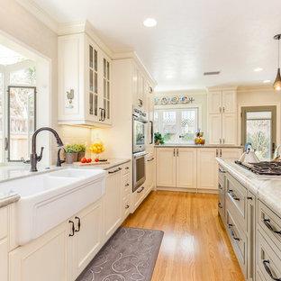Esempio di una grande cucina chic con lavello stile country, ante con riquadro incassato, ante beige, elettrodomestici in acciaio inossidabile, pavimento in legno massello medio, pavimento arancione, top in quarzo composito e paraspruzzi beige