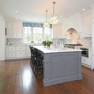This is an example of a traditional u-shaped separate kitchen in Boston with recessed-panel cabinets, white cabinets, white splashback, stainless steel appliances, dark hardwood floors, with island, marble benchtops and cement tile splashback.