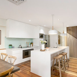 Design ideas for a retro single-wall kitchen/diner in Sydney with a submerged sink, flat-panel cabinets, white cabinets, composite countertops, green splashback, glass sheet splashback, stainless steel appliances, plywood flooring, an island and white worktops.