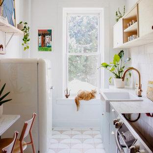 ニューヨークの小さい北欧スタイルのおしゃれなキッチン (エプロンフロントシンク、青いキャビネット、ベージュキッチンパネル、セラミックタイルのキッチンパネル、シルバーの調理設備、セラミックタイルの床、アイランドなし、ベージュの床、白いキッチンカウンター、フラットパネル扉のキャビネット) の写真
