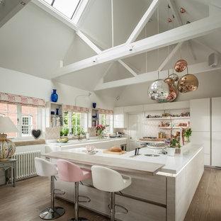ハンプシャーの中サイズのエクレクティックスタイルのおしゃれなアイランドキッチン (フラットパネル扉のキャビネット、白いキャビネット、ピンクのキッチンパネル、無垢フローリング、白いキッチンカウンター) の写真