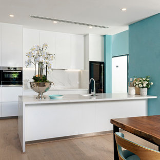 Inspiration for a mid-sized contemporary galley eat-in kitchen in Perth with an undermount sink, flat-panel cabinets, white cabinets, white splashback, black appliances, light hardwood floors, a peninsula, beige floor and white benchtop.