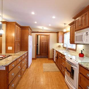 Imagen de cocina de galera, de estilo americano, de tamaño medio, abierta, con fregadero bajoencimera, armarios con paneles lisos, puertas de armario de madera oscura, encimera de laminado, salpicadero beige, salpicadero de azulejos de cerámica, electrodomésticos blancos y suelo de madera clara