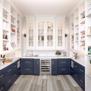 Klassische Küche ohne Insel in U-Form mit Vorratsschrank, Schrankfronten im Shaker-Stil, blauen Schränken, Küchengeräten aus Edelstahl, braunem Holzboden, braunem Boden und weißer Arbeitsplatte in Sonstige