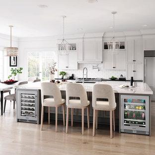 Zweizeilige Klassische Wohnküche mit Unterbauwaschbecken, Schrankfronten im Shaker-Stil, weißen Schränken, Küchenrückwand in Weiß, Rückwand aus Metrofliesen, Küchengeräten aus Edelstahl, braunem Holzboden, Kücheninsel, braunem Boden und bunter Arbeitsplatte in Sonstige