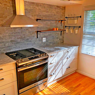 Inspiration for a large cottage single-wall medium tone wood floor and brown floor eat-in kitchen remodel in Detroit with a farmhouse sink, shaker cabinets, white cabinets, granite countertops, gray backsplash, subway tile backsplash, stainless steel appliances, no island and gray countertops