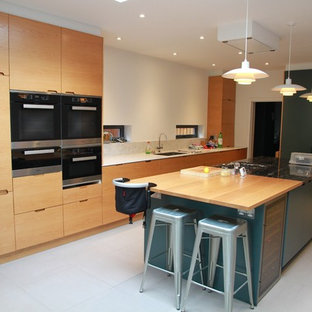 Design ideas for a large contemporary single-wall kitchen/diner in London with flat-panel cabinets, light wood cabinets, stainless steel appliances, an island, a submerged sink, wood worktops, grey floors and brown worktops.