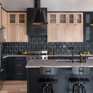 Photo of a large transitional l-shaped eat-in kitchen in Other with a double-bowl sink, shaker cabinets, black cabinets, quartzite benchtops, black splashback, ceramic splashback, stainless steel appliances, light hardwood floors, with island, brown floor, grey benchtop and exposed beam.