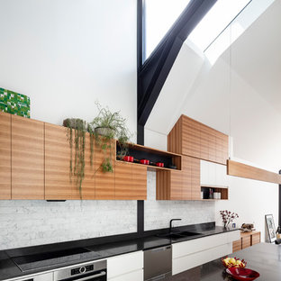 This is an example of a mid-sized contemporary galley eat-in kitchen in Sydney with a double-bowl sink, flat-panel cabinets, white cabinets, quartz benchtops, grey splashback, stainless steel appliances, concrete floors, with island, grey floor and black benchtop.
