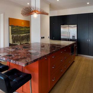 Große Stilmix Wohnküche in L-Form mit Unterbauwaschbecken, Schrankfronten im Shaker-Stil, Granit-Arbeitsplatte, Küchenrückwand in Orange, Glasrückwand, Küchengeräten aus Edelstahl, schwarzen Schränken, braunem Holzboden und Kücheninsel in Melbourne