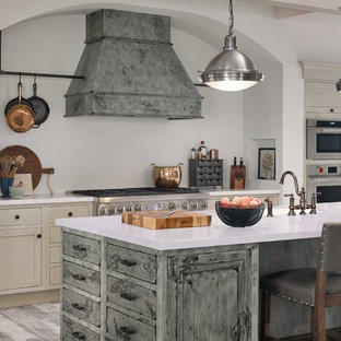 Design ideas for a large transitional l-shaped eat-in kitchen in DC Metro with a farmhouse sink, beaded inset cabinets, white cabinets, quartzite benchtops, beige splashback, slate splashback, stainless steel appliances, porcelain floors, multiple islands, grey floor and multi-coloured benchtop.