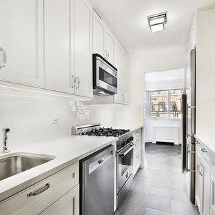 Idéer för att renovera ett avskilt, litet vintage parallellkök, med en undermonterad diskho, luckor med infälld panel, vita skåp, bänkskiva i kvartsit, vitt stänkskydd, stänkskydd i tunnelbanekakel, rostfria vitvaror, skiffergolv och grått golv