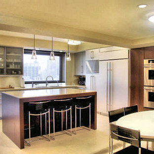 Inspiration for an expansive modern u-shaped separate kitchen in New York with an undermount sink, flat-panel cabinets, stainless steel cabinets, solid surface benchtops, metallic splashback, metal splashback, stainless steel appliances, with island and porcelain floors.