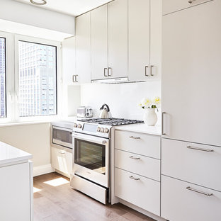 Small contemporary enclosed kitchen pictures - Small trendy u-shaped light wood floor and beige floor enclosed kitchen photo in New York with flat-panel cabinets, white cabinets, stainless steel appliances, an undermount sink, solid surface countertops, white backsplash, stone slab backsplash and no island